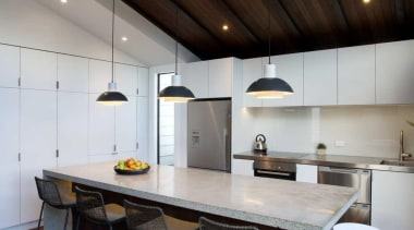 The high ceilings are lined with timber softening architecture, ceiling, countertop, daylighting, floor, furniture, house, interior design, kitchen, real estate, table, wood, brown