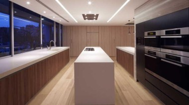 In this contemporary apartment renovation, woodgrain surfaces from cabinetry, countertop, floor, flooring, interior design, kitchen, lighting, room, brown, gray