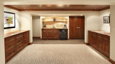 Because of its expansive and wide-open layout, a cabinetry, countertop, cuisine classique, floor, flooring, furniture, hardwood, interior design, kitchen, room, wood, wood flooring, wood stain, orange, brown