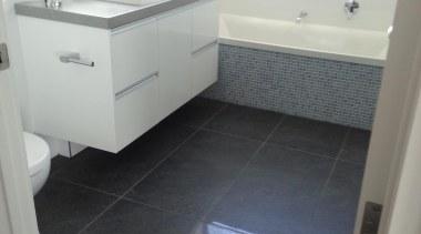 Anthracite bathroom floor with Bisazza Luisa bath feature. bathroom, bathroom accessory, bathroom cabinet, floor, flooring, hardwood, home, laminate flooring, product, property, room, sink, tile, wood flooring, white, gray, black