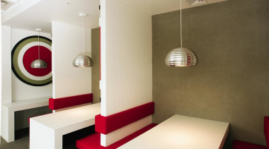 Small booths are painted to reflect another brand. ceiling, floor, interior design, light fixture, lighting, room, table, white, brown