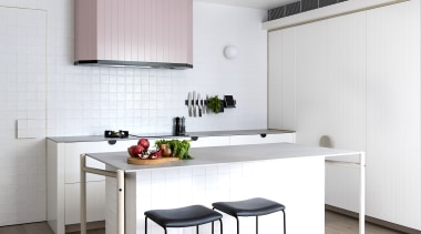 A light pink rangehood provides a quiet feature white