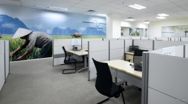 Low partitions between workstations encourage staff interaction. desk, furniture, interior design, office, gray