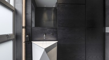 A custom-made timber clad veneer wall acts as