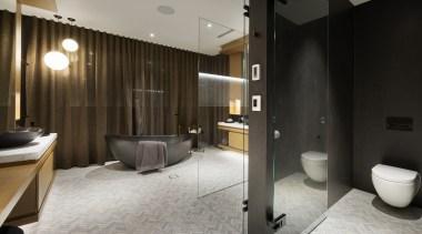 A beautiful freestanding black stone bath sits to