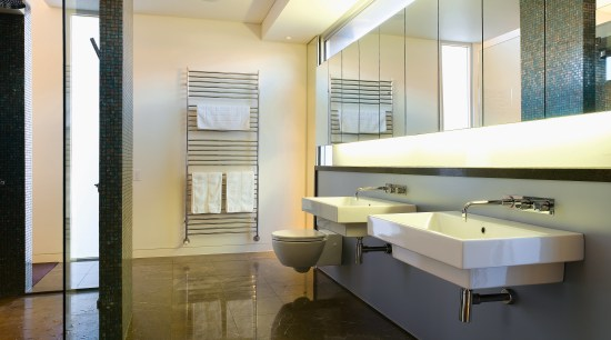 Large wall-hung basins accentuate the size of the architecture, ceiling, daylighting, floor, flooring, interior design, room, wood flooring, white