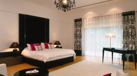A view of the master bedroom. bedroom, ceiling, furniture, interior design, lighting, living room, room, suite, wall, orange