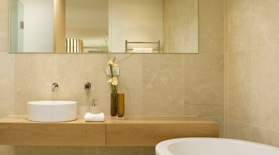 The vanity shelf is cantilevered, for an open, architecture, bathroom, bathroom sink, ceiling, ceramic, floor, flooring, home, interior design, plumbing fixture, product design, room, sink, tap, tile, wall, orange