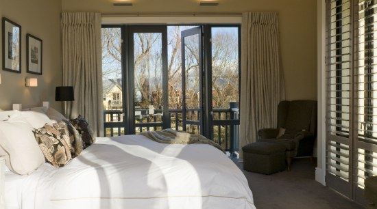 The master bedroom on the upper level has bed frame, bedroom, curtain, estate, floor, furniture, home, interior design, real estate, room, suite, textile, window, window covering, window treatment, wood, brown, white