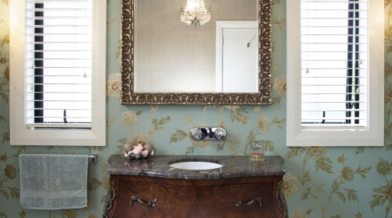 View of bathroom with floral wallpaper and dark-toned antique, bathroom accessory, chest of drawers, furniture, home, interior design, room, table, window, white, gray, brown