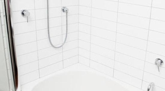 White tiled bathroom with white bath. angle, bathroom, bathroom sink, bathtub, floor, plumbing fixture, product, product design, room, tap, tile, toilet seat, wall, white