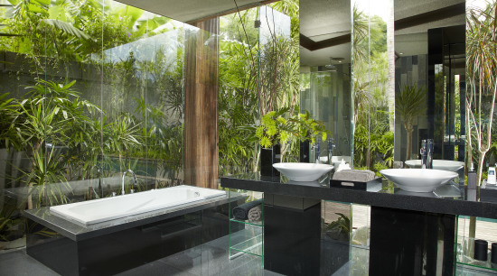 Floor-to-ceiling glass opens up this bathroom to the interior design, brown