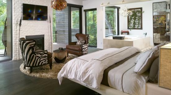 The master bedroom in this modern home is bed frame, bedroom, floor, flooring, furniture, home, interior design, living room, room, window, wood, gray