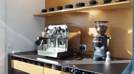 This dedicated coffee center provides storage for cups, countertop, interior design, kitchen, gray, black