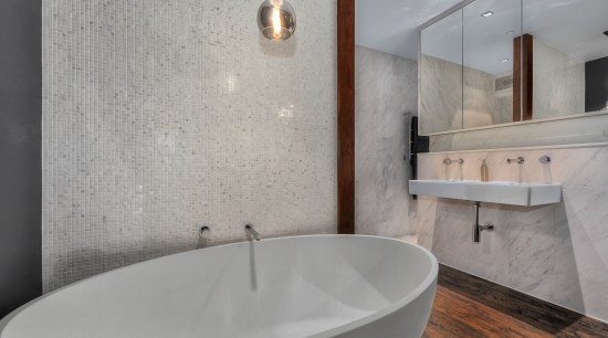 Large mirrors above the bathroom vanity conceal storage bathroom, bathroom sink, bidet, ceramic, floor, interior design, plumbing fixture, product design, room, sink, tap, tile, gray