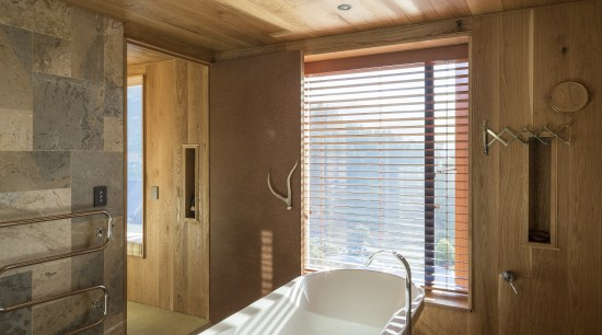 This freestanding bathtub is positioned in front of architecture, ceiling, estate, floor, home, house, interior design, property, real estate, room, wall, window, wood, brown