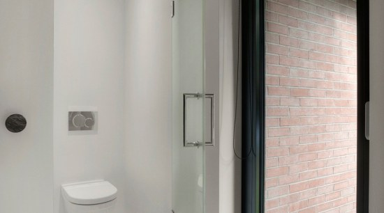 The toilet has it's own separate enclosure in architecture, bathroom, building, daylighting, door, floor, glass, house, interior design, plumbing fixture, property, real estate, room, tile, window, gray