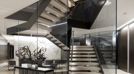 Visitors encounter a dynamic glass and steel staircase architecture, black-and-white, building, ceiling, daylighting, design, floor, limestone floor,  stair, staricase, glass, handrail, house, interior design, line, lobby, material property, metal, real estate, room, stairs, gray