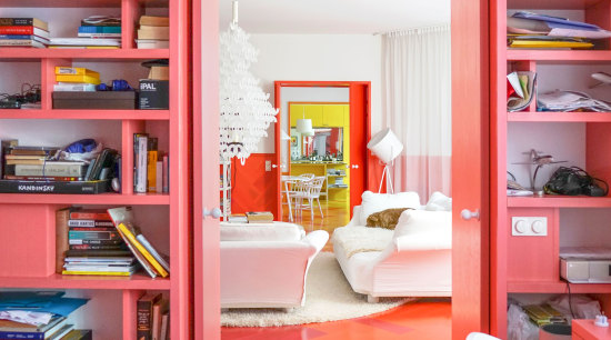 Anything but a typical Scandinavian interior with a architecture, bookcase, building, ceiling, floor, flooring, furniture, home, house, interior design, living room, orange, pink, property, red, room, shelf, shelving, table, wall, yellow, red