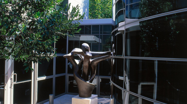 Large sculpture in courtyard surrounded by contemporary house architecture, house, outdoor structure, plant, tree, window, black