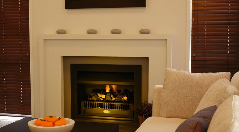 Fireplace with cream surround, ornaments on mantel and fireplace, hearth, interior design, living room, wood burning stove, brown, orange