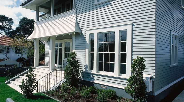 Two storey weatherboard home with balcony, steps, garden backyard, cottage, facade, home, house, porch, property, real estate, residential area, siding, window, yard, black, white