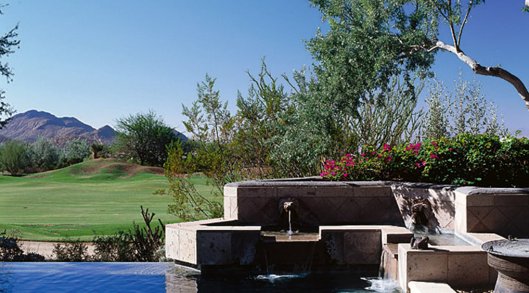 Close view of the water feature located beside backyard, estate, home, landscape, landscaping, leisure, plant, property, real estate, sky, swimming pool, tree, villa, water, water feature, teal