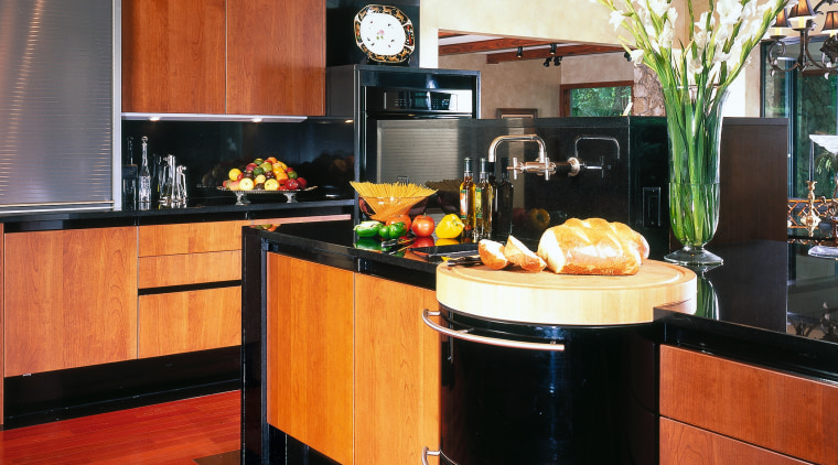Professional kitchen. Kitchen island with a curved butcher's cabinetry, countertop, flooring, hardwood, interior design, kitchen, room, black