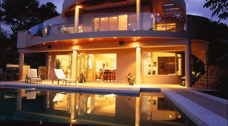 Exterior of house looking over pool back to architecture, estate, evening, home, house, landscape lighting, lighting, property, real estate, reflection, swimming pool, villa, black