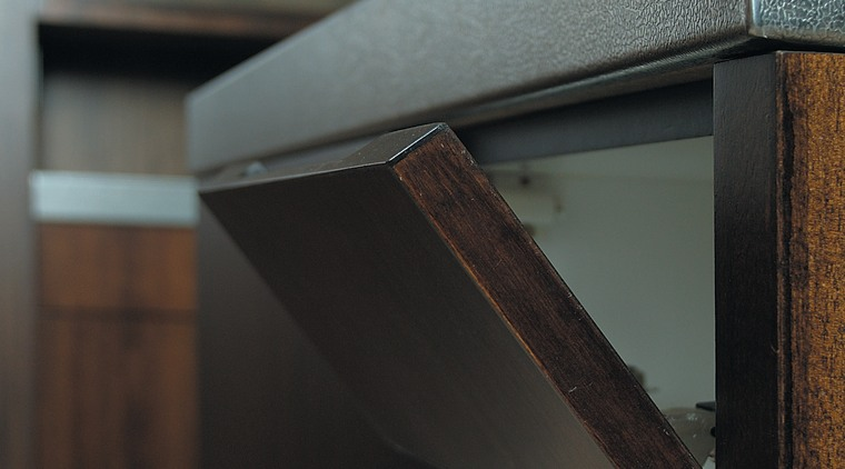 The detail of a flip down flap on furniture, product design, wood, black