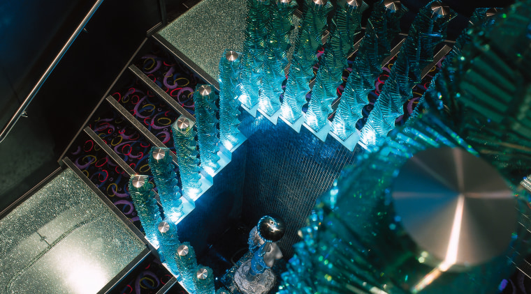 Stairway with glass balustrades lit up by blue light, black, teal
