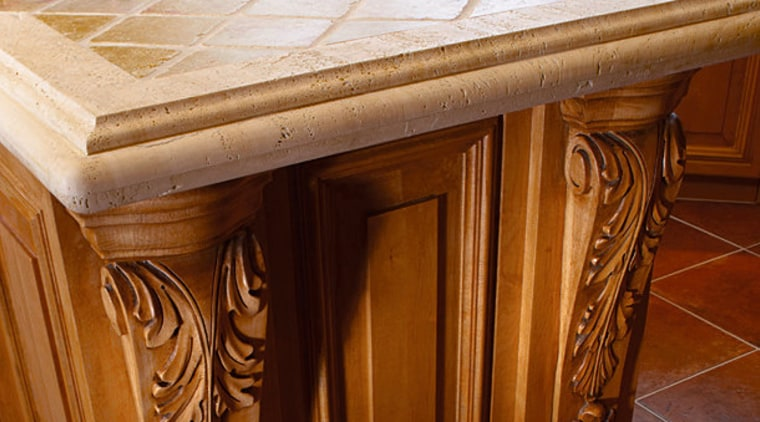 Kitchen island with ornate corbels, custom-made and installed cabinetry, carving, countertop, floor, flooring, furniture, hardwood, table, wood, wood stain, brown