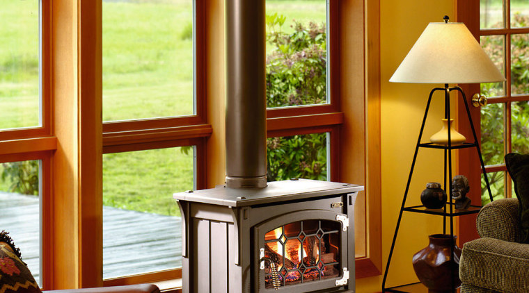 The Avalon Prairie gas stove in this living fireplace, furniture, hardwood, hearth, home, home appliance, interior design, living room, window, window covering, wood, wood burning stove, brown