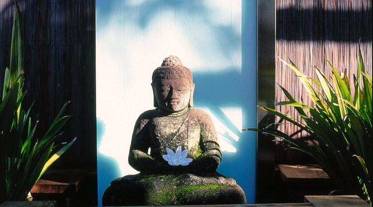 Water feature with traditional Buddha sculpture and glass flower, grass, plant, sunlight, window, black