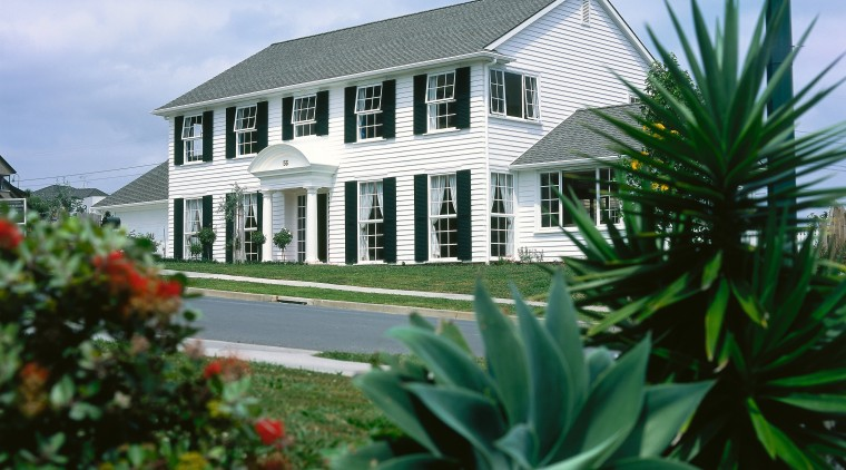 A photograph of a two storey house with building, cottage, estate, home, house, plant, property, real estate, villa, teal