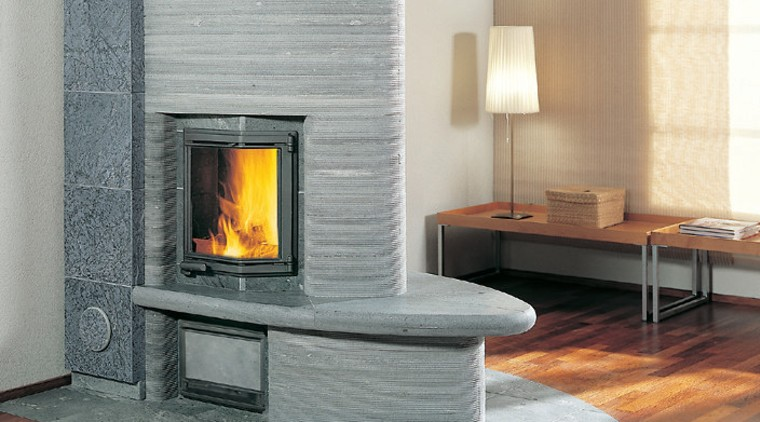 A photograph of a curved fireplace. The area fireplace, floor, flooring, hearth, heat, home appliance, wood burning stove, gray