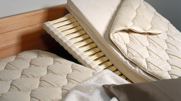 A photograph of the insides of a Huesler bed, bed frame, floor, flooring, furniture, mattress, mattress pad, product, product design, gray