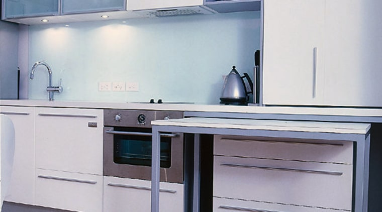 A pull-out mobile table features in the kitchen. cabinetry, countertop, furniture, home appliance, kitchen, major appliance, product, product design, gray