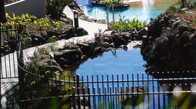 Exterior view of landscaped garden showing water features arecales, leisure, outdoor structure, palm tree, plant, pond, reflection, resort, swimming pool, tree, water, water feature, black