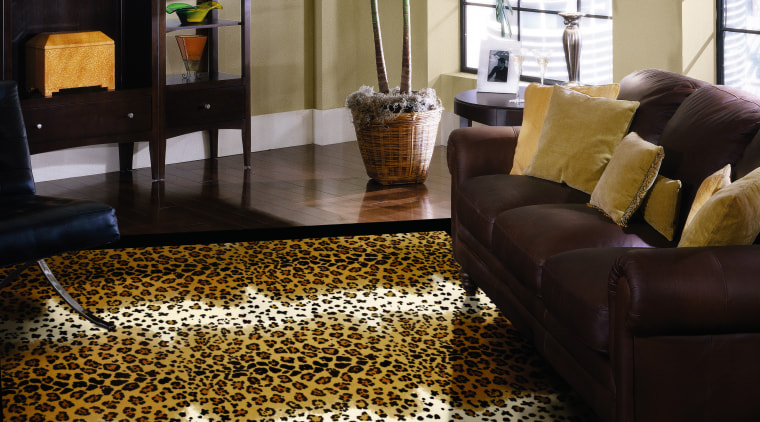View of this animal print floor rug by carpet, floor, flooring, hardwood, home, interior design, living room, wood flooring, black, brown