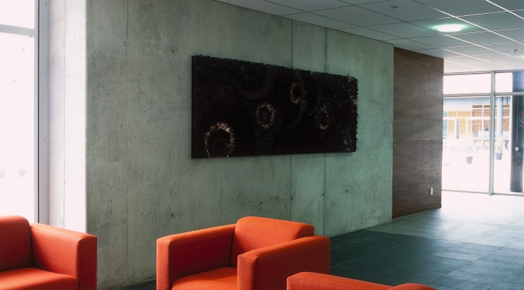 Lobby of building with concrete wall, floor tiles, architecture, ceiling, floor, furniture, interior design, lobby, table, wall, gray