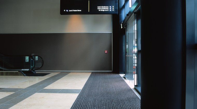 Entrance way of convention centre with long striped architecture, floor, flooring, black