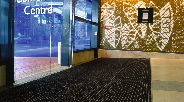 Entranceway of convention through glass doors with striped flooring, black