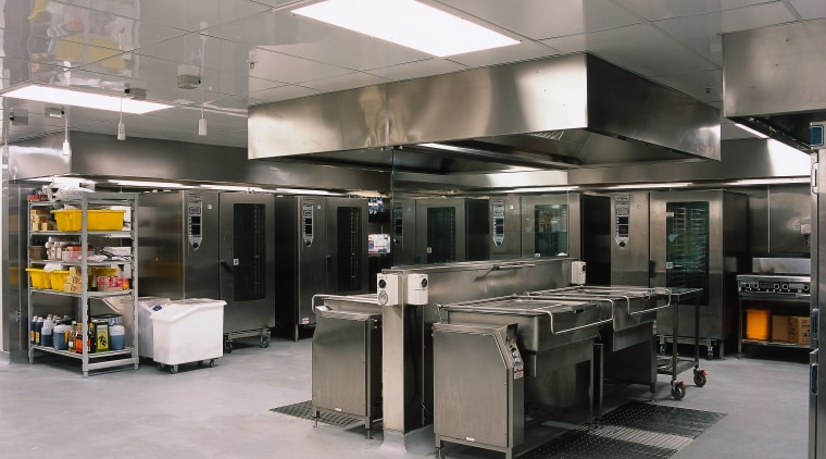 Commercial kitchen with stainless steel equipment including ovens gray