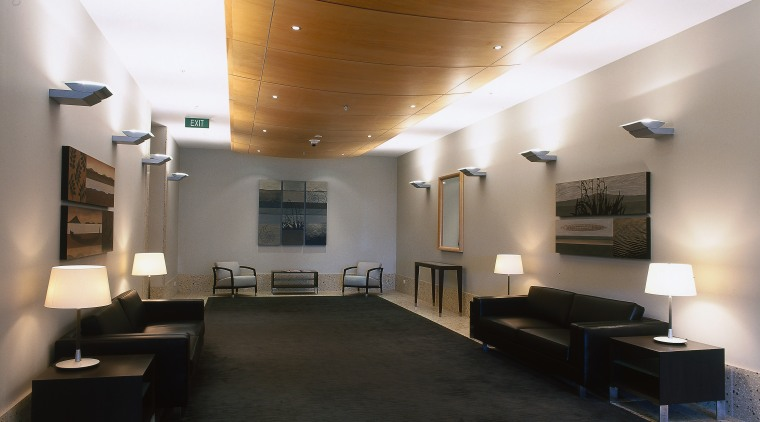 The lobby of this apartment building has curved architecture, ceiling, daylighting, floor, flooring, interior design, lobby, black, gray