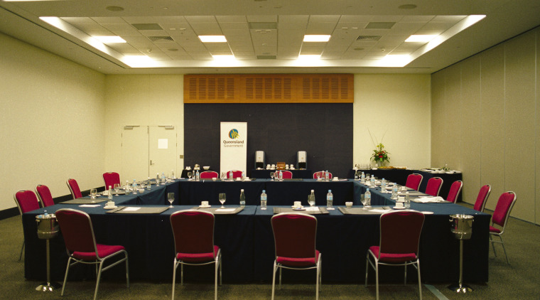 Meeting room with neutral coloured walls, square shaped conference hall, function hall, table, brown