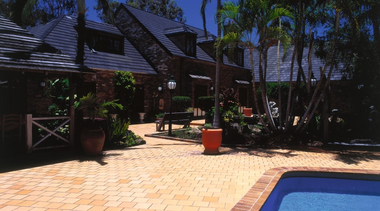 Exterior of house with brick cladding, dark grey arecales, backyard, estate, home, leisure, lighting, outdoor structure, palm tree, property, real estate, resort, swimming pool, tree, vacation, villa, walkway, black, orange