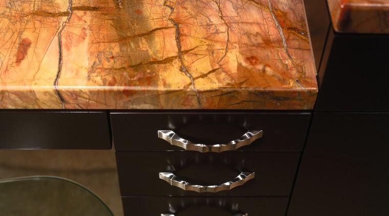 Closeup of bathroom vanity with gold coloured granite floor, flooring, furniture, hardwood, table, wall, wood stain, black