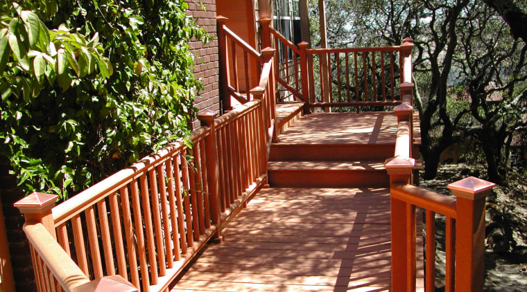 Exterior view of a wooden decking system and backyard, cottage, deck, handrail, home, house, outdoor structure, plant, property, real estate, tree, walkway, wood, yard, red
