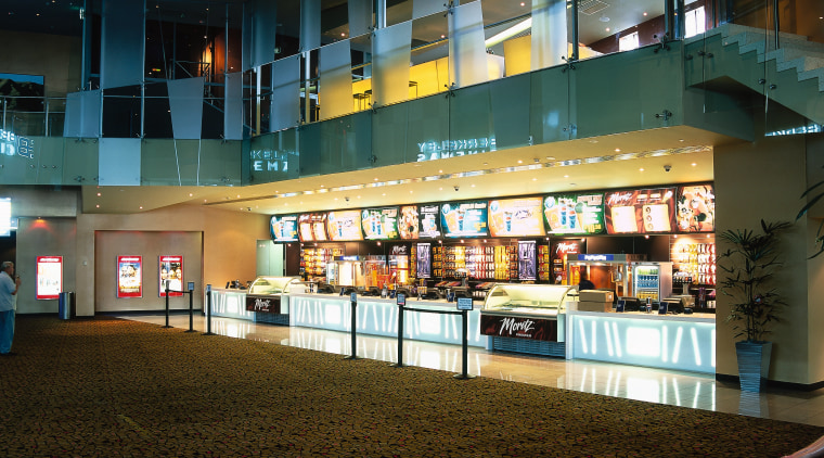 Retail shop area of cinema complex with bright architecture, metropolitan area, night, reflection, shopping mall, black